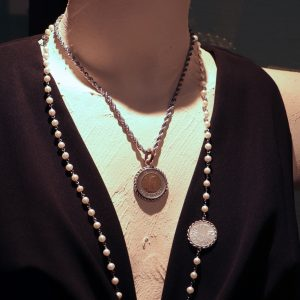 Unikate: Ketten aus Stahl, zum Teil mit Süsswasserperlen. Zentrales Motiv: in Silber eingefasste antike Münzen.